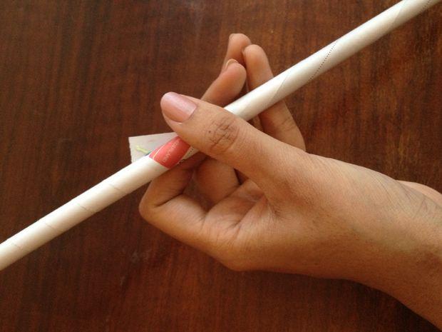 Кончик также запечатайте клеем, но теперь надежно удерживайте уголок на месте пальцем, пока клей не подсохнет