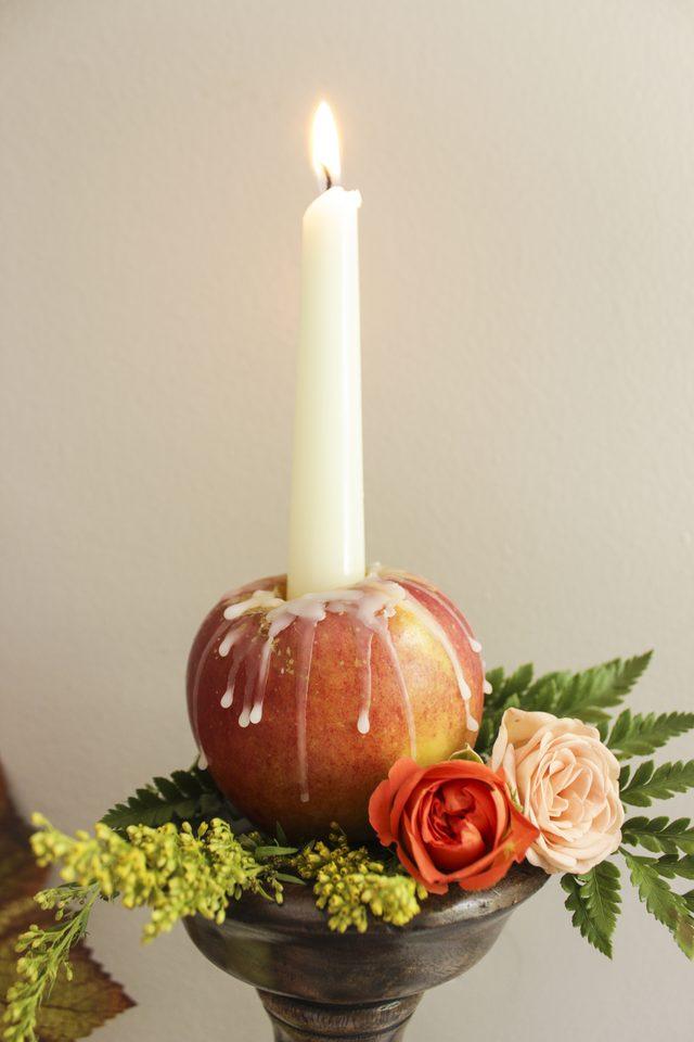 Красиво подобные свечи в свежих яблоках смотрятся в окружении овощей и фруктов, а также свежих и сухих растений