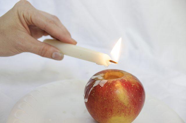 В случае высокой свечи вытаскиваем ее из яблока и зажигаем, а капли и потеки воска делаем, наклоняя свечу к тоже немного наклоненным бокам яблока
