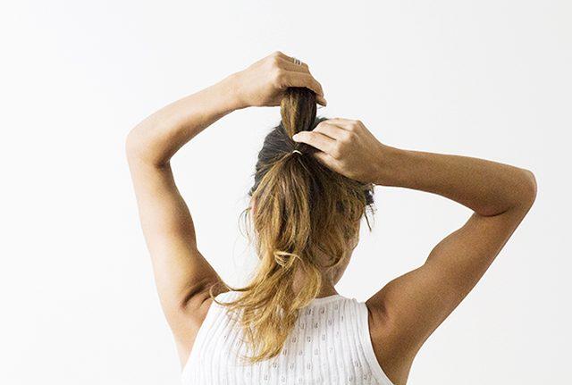 Затем протягиваем нижний хвост волос наверх в образовавшуюся на шаге первом прогалину и опускаем второй хвост прямо на первый