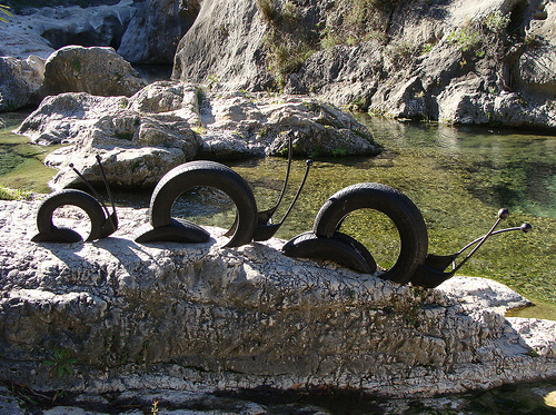 улитки из автомобильных шин на камнях, как часть креативного ландшафтного дизайна