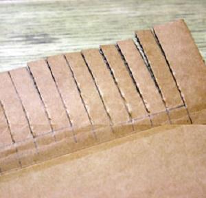 По меткам нарезаем верх картона на бахрому до линии, стараясь не смягчать картон