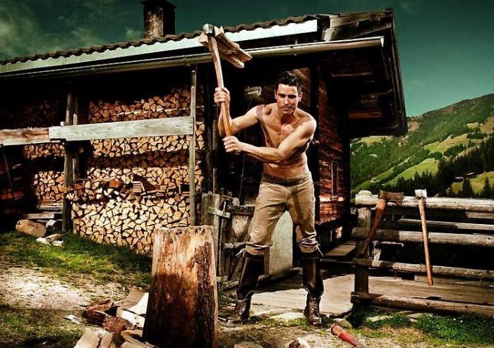 парень без рубашки рубит дрова на жаре