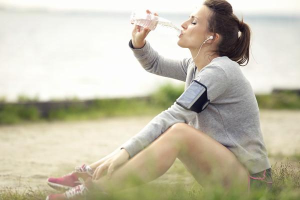 девушка пьет кокосовую воду после пробежки