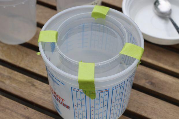 Малярным скотчем или любым его аналогом в 4-х местах по кругу сверху приклеиваем тары друг к другу, чтобы ничего не двигалось во время заморозки