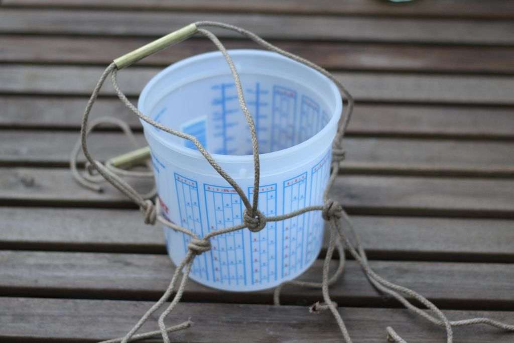 Теперь берите внешнюю тару из-под ледяного ведерка и надевайте готовый верх сетки на контейнер, ровно распределяя тот первый ряд узлов по кругу