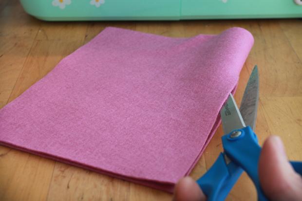 Сложите фетр пополам, соединяя более короткую сторону прямоугольника со второй короткой, разрежьте по сгибу