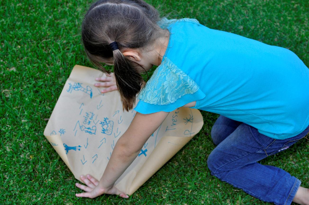 девочка рассматриват карту по охоте за сокровищами