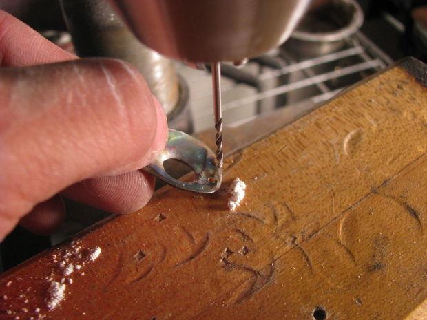 Очень аккуратно, следя за пальцами, сверлим сверху в отполированном кусочке ракушки маленькое отверстие, применяя малое давление