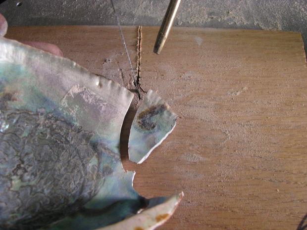 Электро- или обычным лобзиком отпиливаем от ракушки кусочек, который будем шлифовать