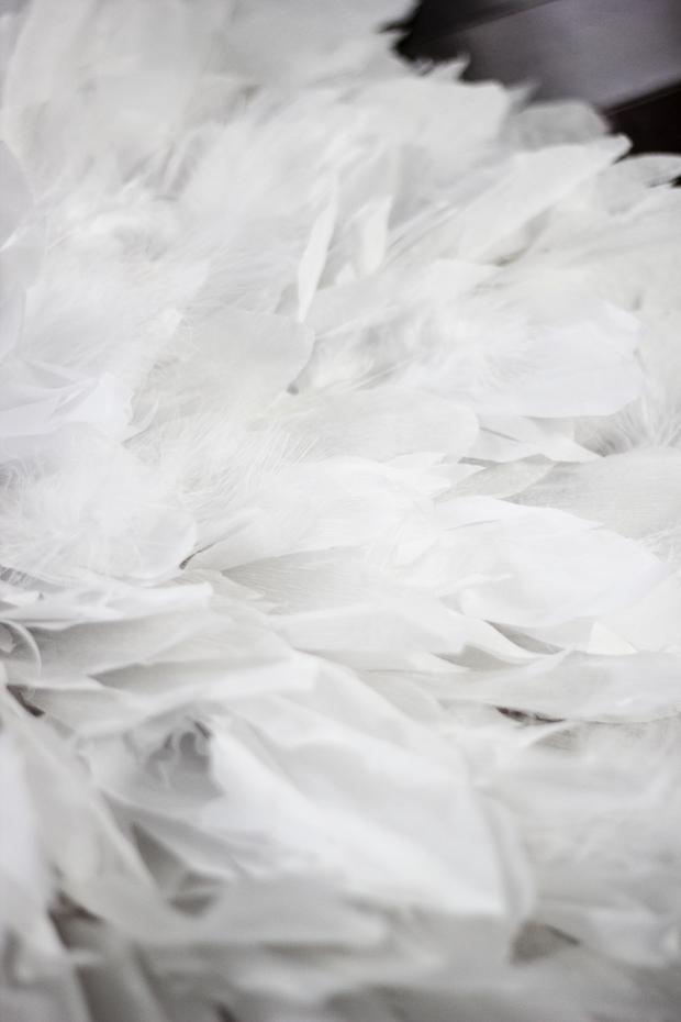 Самые крупные бумажные перья клеим по внешнему краю картонного круга-основы. Затем делаем второй ряд-круг из настоящих перьев – чуть ниже