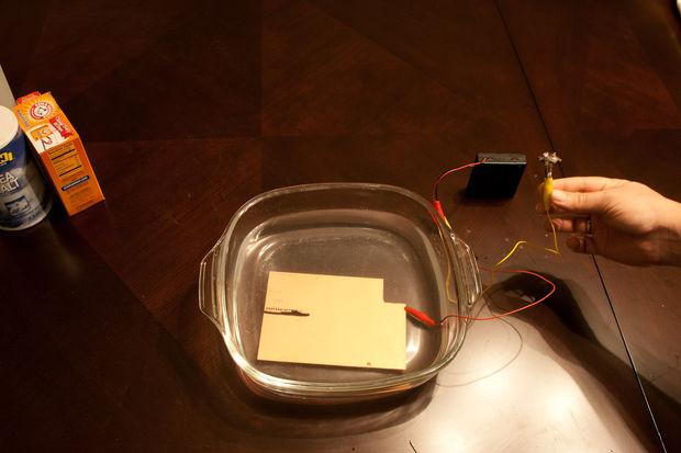 Прикрепляем кусок меди, предпочтительно с большой поверхностью, к плюсу источника постоянного тока, погружаем медь в воду с солью и содой; прикрепляем минус к кольцу.