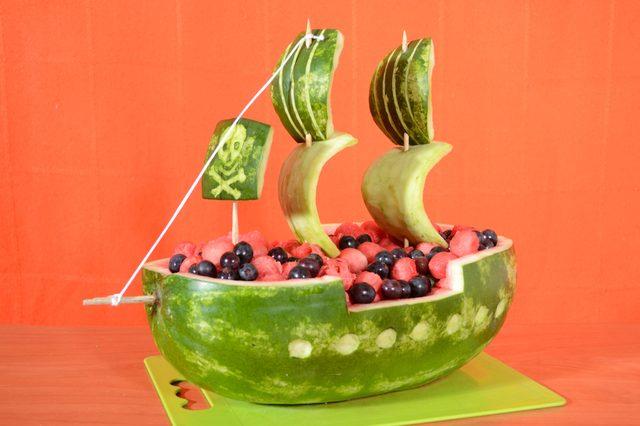 Корзинки, вырезанные из арбуза, - очаровательное и освежающее дополнение к сервировке стола или бара на банкете, вечеринке или просто семейном обеде. В подобные корзинки кладут кусочки арбуза, очищенные от косточек, дыни, ягоды (в т.ч. виноград), фруктовые салаты, лед и что угодно еще, подходящее по вкусу.   Вам потребуются: - Крупный арбуз – и не обязательно именно вытянутой формы; - Крупный нож (желательно специальный для карвинга, но можно и обычный - шеф); - Перманентный маркер или темный фломастер; - Столовая ложка или специальная ложечка для получения шариков из мякоти арбуза/дыни; - Крупная миска; - Прецизионный нож (или любой миниатюрный кухонный нож); - Инструмент для чистки овощей и другие ножи/инструменты, наиболее удобные для вырезания отдельных мелких деталей корабля; - Деревянные шампуры; - Тонкий шнурок, небольшой кусок.   1. С нижней части арбуза – той, что сбоку наиболее плоская изначально - срезаем тонкую широкую полоску/овал кожуры, делая ровную плоскую основу для устойчивости будущего корабля. Аккуратнее – не срежьте слишком много, т. е. не до мякоти, иначе корабль «даст течь»!!  2. Ставим арбуз на срезанную часть, и сбоку по всему кругу намечаем маркером контур верхнего края корабля. Для этого сверху отступаем примерно 2,5 см (если арбуз круглый, просто делайте наметку чуть выше «экватора» положенного на бок арбуза) и рисуем с каждого бока горизонтальную линию от попки или «хвостика» до трети длины арбуза. От этой точки далее рисуем вниз вертикальную линию примерно на 3,8-5 см (в зависимости от ширины арбуза). От последней точки опять горизонтальную линию – еще на 1/3 длины арбуза. Затем снова вертикальную линию до прежнего уровня, потом снова горизонтальную на последнюю треть длины арбуза. Посередине сбоку получается перевернутая широкая «П». Уровни линий на обоих боках арбуза должны совпадать.  3. Длинным острым ножом разрезаем арбуз по этой наметке. Разрезы делайте как можно более чистыми, используя «пилящее» движение ножом. Аккуратно, не раз