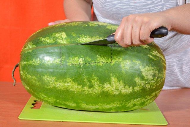 Длинным острым ножом разрезаем арбуз по этой наметке