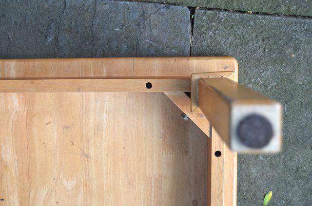 Переворачиваем журнальный столик ножками вверх и вывинчиваем удерживающие столешницу винты из рамы стола