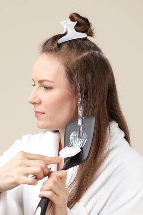 Заколите верхний слой волос, начиная с 7,6 см от корней, используя кисть, протащите высвечивающий пигмент вдоль пряди