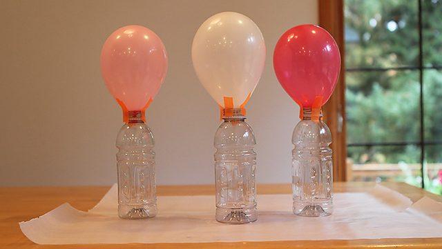 Надуваем шарики – лучше разного размера - и надежно крепим их к открытым горлышкам бутылок при помощи нескольких кусочков скотча