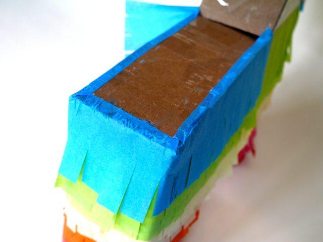 Верхнюю часть следующей по очереди полоски просто перегните через край и наклейте на спину горизонтально