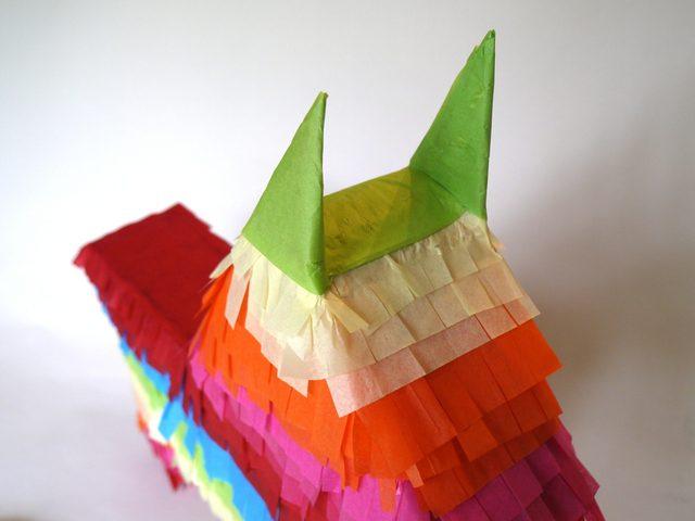 Ушки и верхушку головы заклеиваем полосками крепированной бумаги уже без бахромы, но оборачивая уши в бумагу