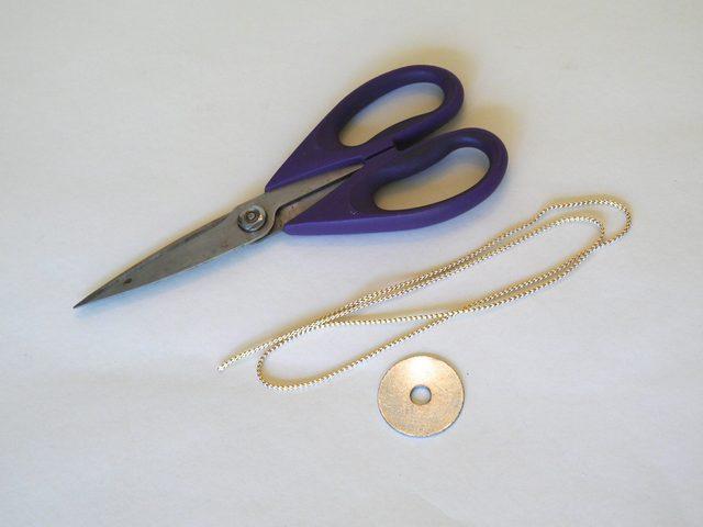 Возьмите тесьму или провод примерно 20 см длиной. Возьмите шайбу диаметром около 5 см с маленьким отверстием по центру.