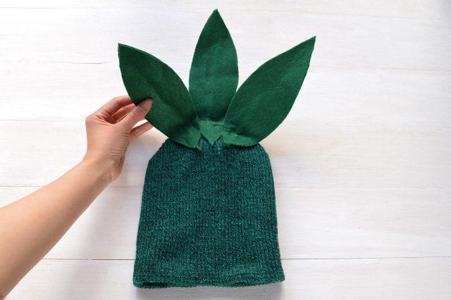Эти листья наклеиваем горячим клеем на зеленую вязаную шапочку сзади веером, затем немного подгибаем