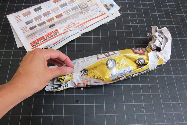 Скомкайте пару газетных листов в руках и оберните вокруг них еще один, заклейте концы последнего листа липкой лентой