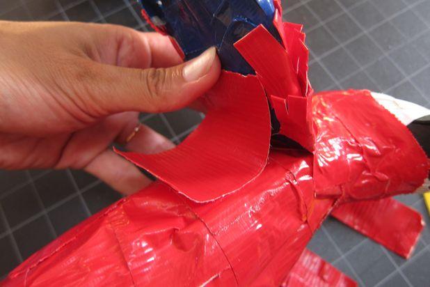 Большим куском красной ленты приклейте каждое крыло сверху с тыльной стороны к попугаю