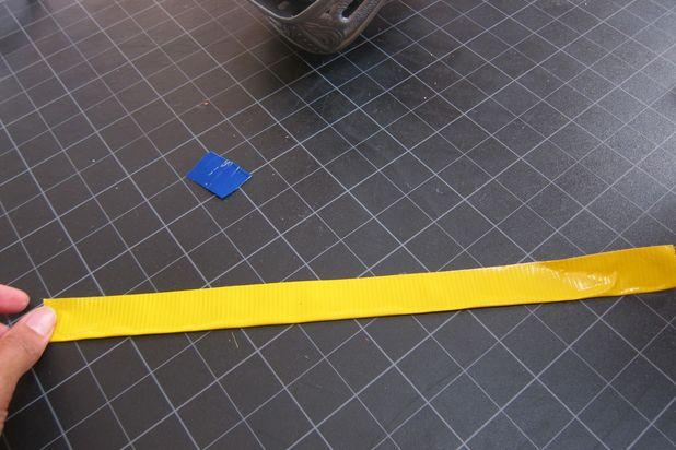 Нарежьте 16 полосок цветной липкой ленты по 20-30 см и по всей длине сложите их ровно в половину
