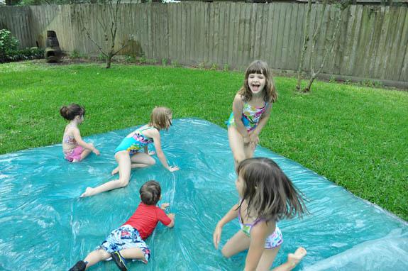 Водяной «пузырь»: креативно развлечь детей на даче - катание/скольжение на мокрой клеенке