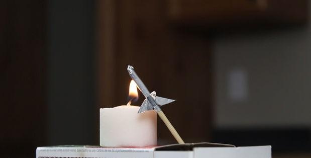 Зажгите малую свечку и поставьте ее так, чтобы пламя находилось прямо под верхним кончиком ракеты