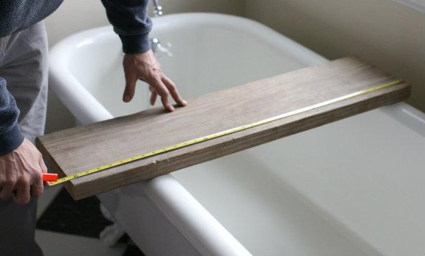 Снимите мерки, где пилить, приложив доску прямо к ванной