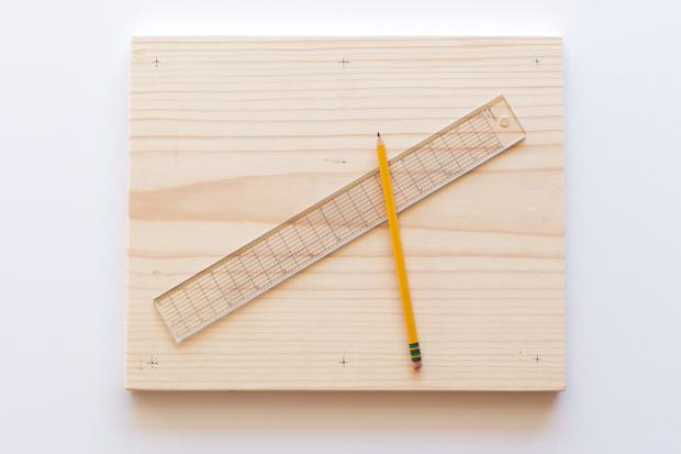 Возьмите деревянные доски, поставьте на каждой из них с тыльной стороны крестики-метки для сверления отверстий по углам и в центре на длинных сторонах