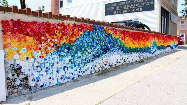 Мозаика из цветных пластиковых крышек на кирпичной стене