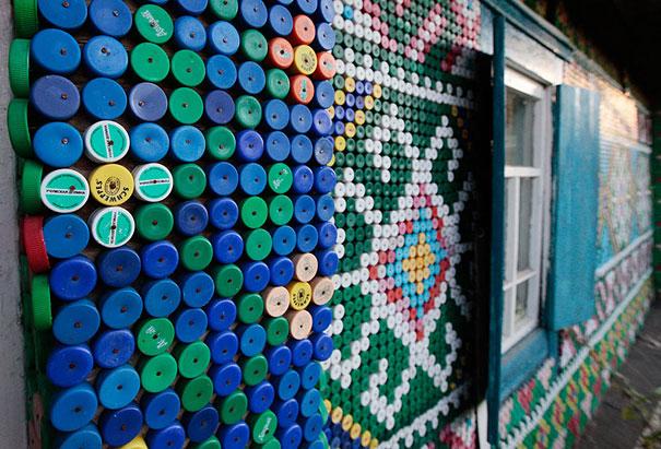 Мозаика из цветных пластиковых крышек - российский традиционный вариант на деревянном доме