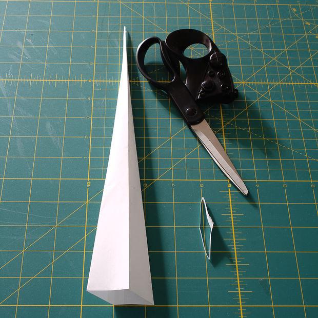 Откройте конус, совместите склеенный шов конуса и боковой сгиб, прижмите, создавая дополнительные сгибы по сторонам и получая что-то вроде длинной 4-х гранной пирамиды