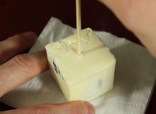 Чем-то вроде деревянного шампура (тонким и острым на конце) протыкаем ровно по центру первой половинки масла отверстие – вниз до самого конца