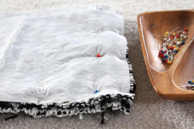 Накладываем 2 детали из свитера друг на друга лицевая к лицевой и скалываем булавками бока и нижнюю часть будущей сумки