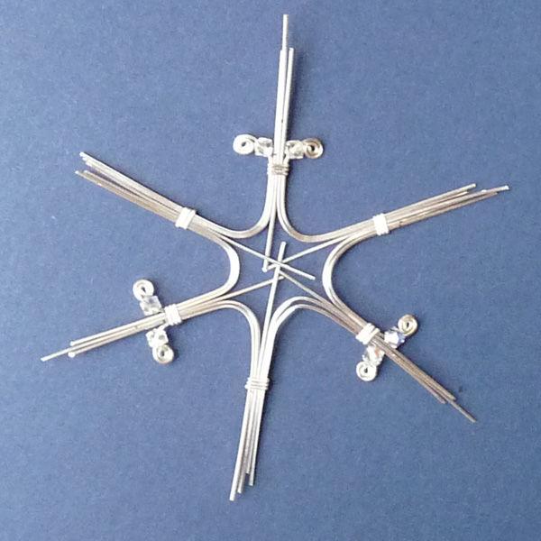 Берем по 1-му куску проволоки сверху нашей звезды справа и слева, чуть отгибаем, на каждый нанизываем по 1-му кристаллу-бусине, кончики завиваем в спирали