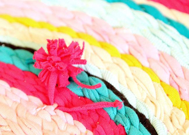 Делаем помпоны, как из обычной пряжи (как – см. в этой статье), и пришиваем или привязываем их в выбранных местах на коврик. Также делаем бахрому из 2-х коротких кусочков пряжи.