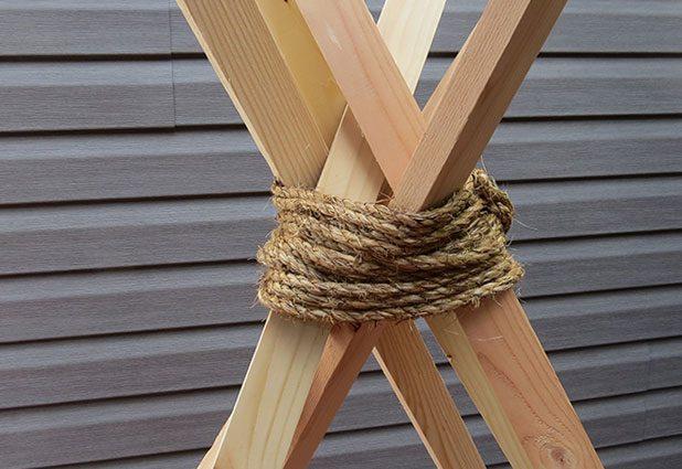 обмотайте как можно туже и крепче веревку вокруг места пересечения брусьев