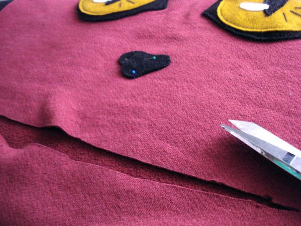 Наметьте на свитере и вырежьте по наметкам ровный горизонтальный рот-линию
