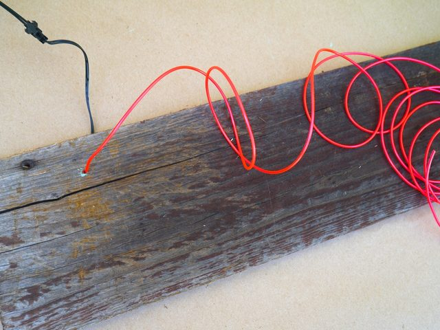 Просовываем кончик провода через просверленное отверстие с тыльной стороны доски наружу.