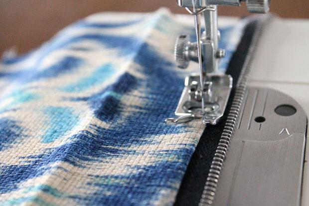 Прошейте молнию и ткань по еще одному разу справа и слева, только теперь с лицевой стороны и отступом от сгибов ткани на молнии в 0,6 см