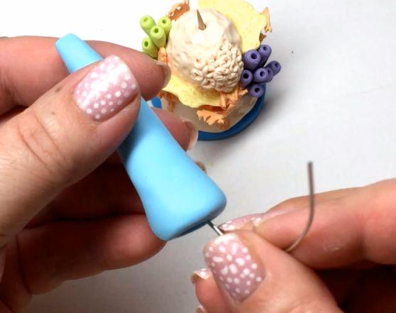 Сформируйте из голубой полимерной глины высокий усеченный конус, вставьте в него алюминиевую проволоку