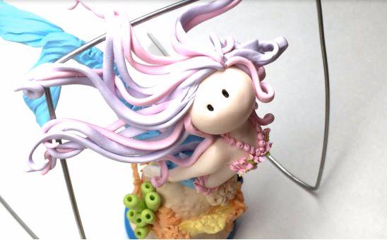 Начинайте из тонких и как можно более ровных колбасок добавлять разноцветные волосы на голову русалочки, красиво укладывая их вокруг головы, друг на друга, немного перевивая друг с другом и опирая кончики «прядей» на качели-подставку, чтобы волосы развивались
