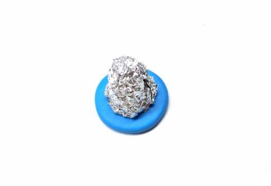 Скомкайте кусок алюминиевой фольги и придайте ей форму колокола с диаметром основания в 1,5 раза меньше голубого основания. Поставьте деталь из фольги на основание.
