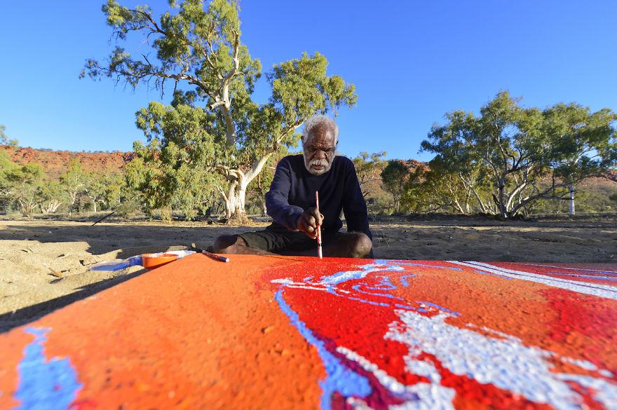 Яннима Пикарли, художник, рисует картину на улице