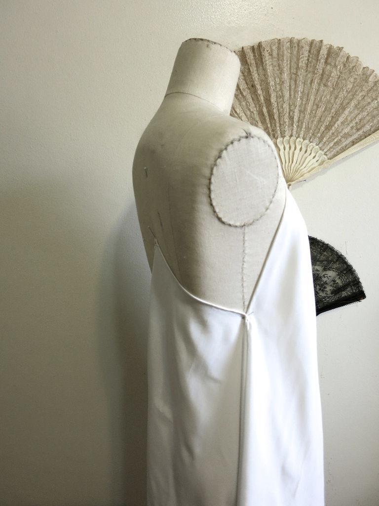 Примерьте полученное и, добавив за уголок по центру спины третий шарф, определите, насколько низкими вы хотите видеть проймы рукавов.
