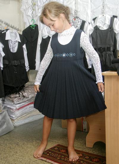 девочка примерет школьную форму с вышивкой и кружевной ажурной блузкой блузой