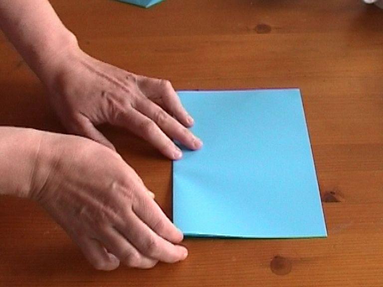 Как нарезать много абсолютно одинаковых снежинок: правильно складываем бумагу, пошаговая инструкция в картинках - сложенный пополам лист, начинаем складывать еще раз пополам, но уже вверх